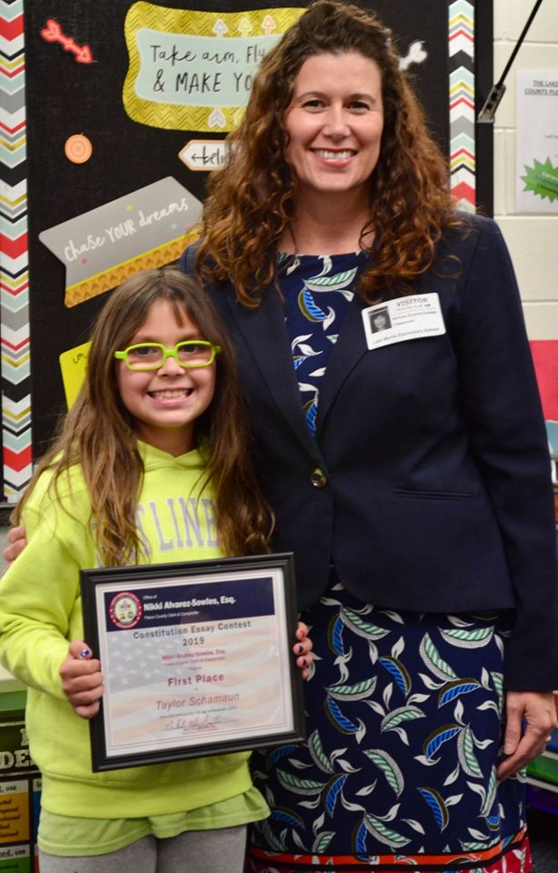 First-prize winner Taylor Schamaun, of Lake Myrtle, with Clerk & Comptroller Nikki Alvarez-Sowles.